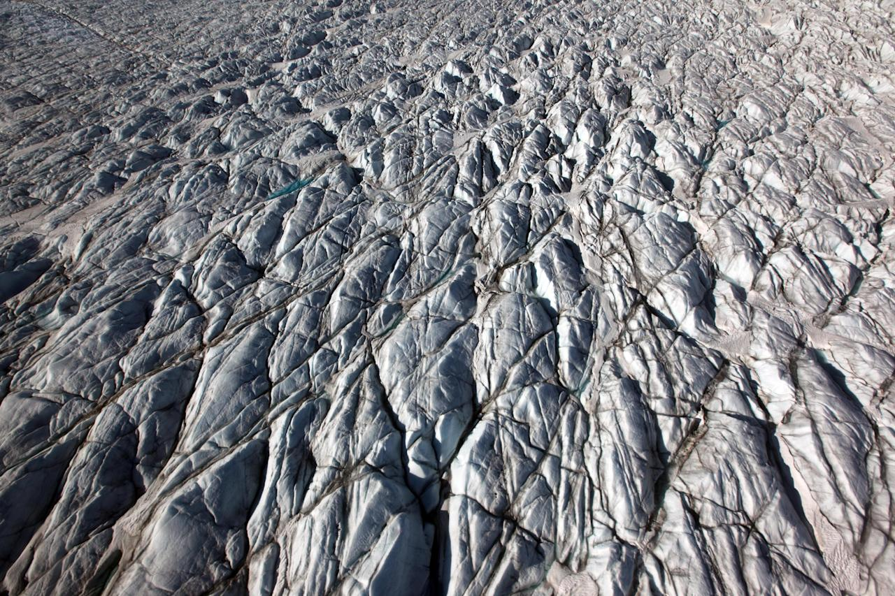 In this July 19, 2011 photo, ridges formed by pressure shape the surface of Jakobshavn Glacier, near the edge of the vast Greenland ice sheet. (AP Photo/Brennan Linsley)