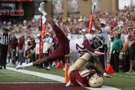 Boston College wide receiver Kobay White (9) scores on a pass reception against Virginia Tech defensive back Jermaine Waller (28) during the first half of an NCAA college football game in Boston, Saturday, Aug. 31, 2019. (AP Photo/Michael Dwyer)
