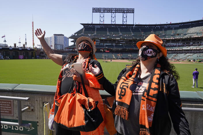 Jeanne Sweet, left, and her sister Erin Sweet, of Sebastopol, Calif., react while seeing their seats and friends in the outfield bleachers before the start of an opening day baseball game between the San Francisco Giants and the Colorado Rockies, Friday, April 9, 2021, in San Francisco. (AP Photo/Eric Risberg)