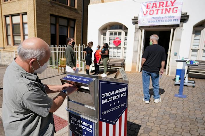 A man drops off his ballot during early voting Oct. 19 in Athens, Ga. A review of the Heritage Foundation's voter fraud database shows the issue of fraud is not as pervasive as some contend.