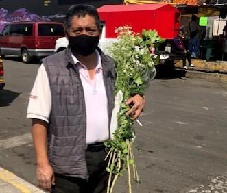 A man in a mask cradles a bouquet of flowers in his left arm
