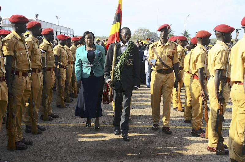 Ugandan Olympic Gold medallist marathon champion Stephen Kiprotich, holding the Ugandan flag centre  accompanied by Education and Sports Minister Jessica Alupo, centre left, inspect a guard of honor,  at Entebbe International Airport 42 kms from the capital Kampala, Uganda, Wednesday Aug. 15, 2012.  Kiprotich's win has been deeply felt  in Uganda, which had not won gold since the Munich Games in 1972. Lawmakers are considering a motion that declares Kiprotich a national hero, his employer has promised to promote him at work. (AP Photo/ Stephen Wandera)