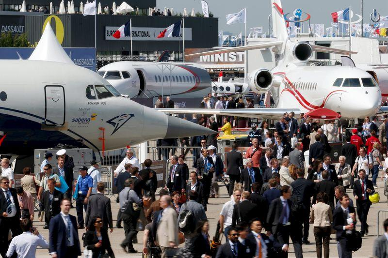 Visitors walk at the static display area during the 51st Paris Air Show at Le Bourget airport near Paris