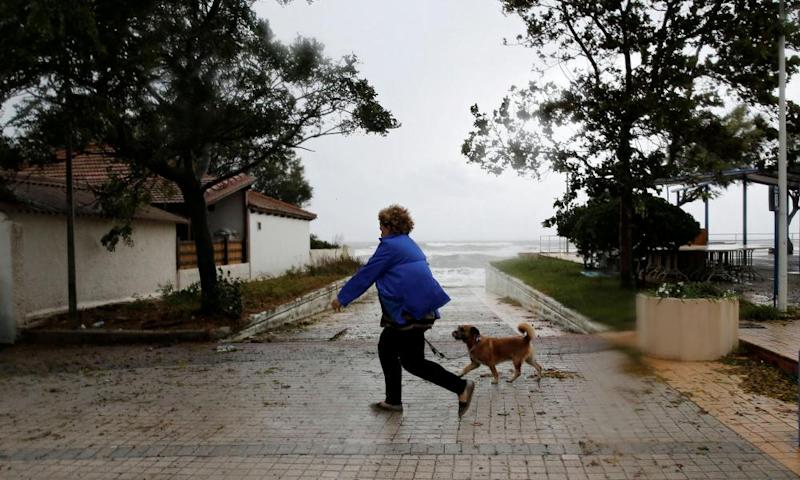 A woman walks her dog near the sea near tAmaliada.