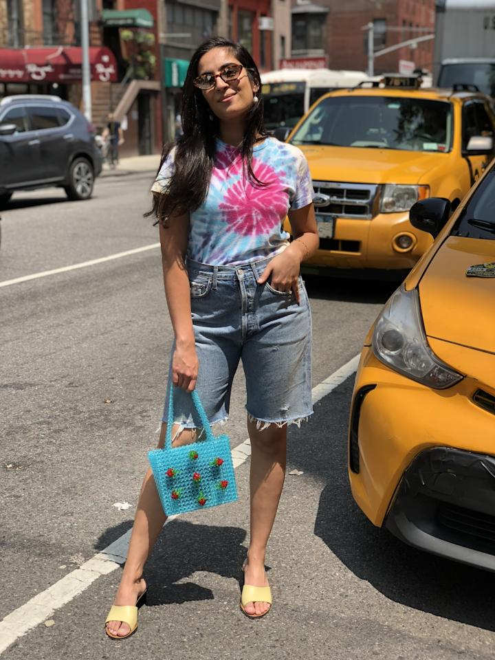 """<p>""""Since my AGOLDE shorts had a baggy silhouette that screamed '90s, I completed the look with another major retro trend of the Summer: tie-dye. I tucked my Re/Done tie-dye shirt into my Bermuda shorts and finished the look with lemon-hued sandals by ATP Atelier. TBH, it really didn't feel any different from wearing a pair of cutoffs or mom jeans and I felt very comfortable walking around the city in these. I finished my outfit off with my favorite Susan Alexandra beaded bag and Warby Parker sunglasses.""""</p>"""