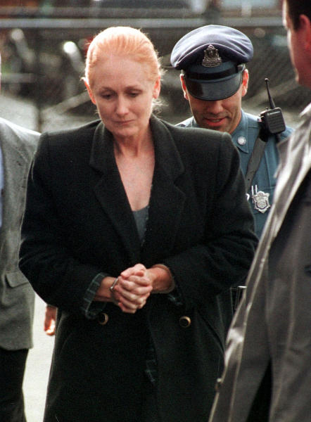 """FILE - In this Nov. 8, 1999 file photo, Margaret Rudin is escorted by police into Framingham District Court in Framingham, Mass., before her arraignment on charges in connection with the shooting death of her husband. On Friday, Jan. 10, 2020, Rudin was released from prison, more than 25 years after her millionaire husband's burned body was found outside Las Vegas and 20 years after a tip generated by a """"most wanted"""" TV show led to her arrest while living in Massachusetts with a retired firefighter she met in Mexico. (AP Photo/Michael Dwyer, File)"""