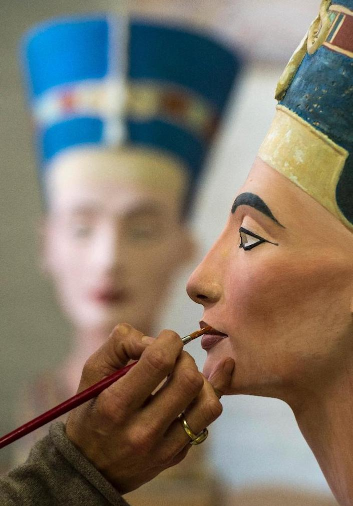 Johanna Gassmann paints a replica of the bust of Nefertiti in Berlin on October 2, 2015 (AFP Photo/John MacDougall)