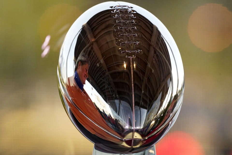 A man looks at the Lombardi Trophy at the NFL Experience Thursday, Feb. 4, 2021, in Tampa, Fla. The city is hosting Sunday's Super Bowl football game between the Tampa Bay Buccaneers and the Kansas City Chiefs. (AP Photo/Charlie Riedel)