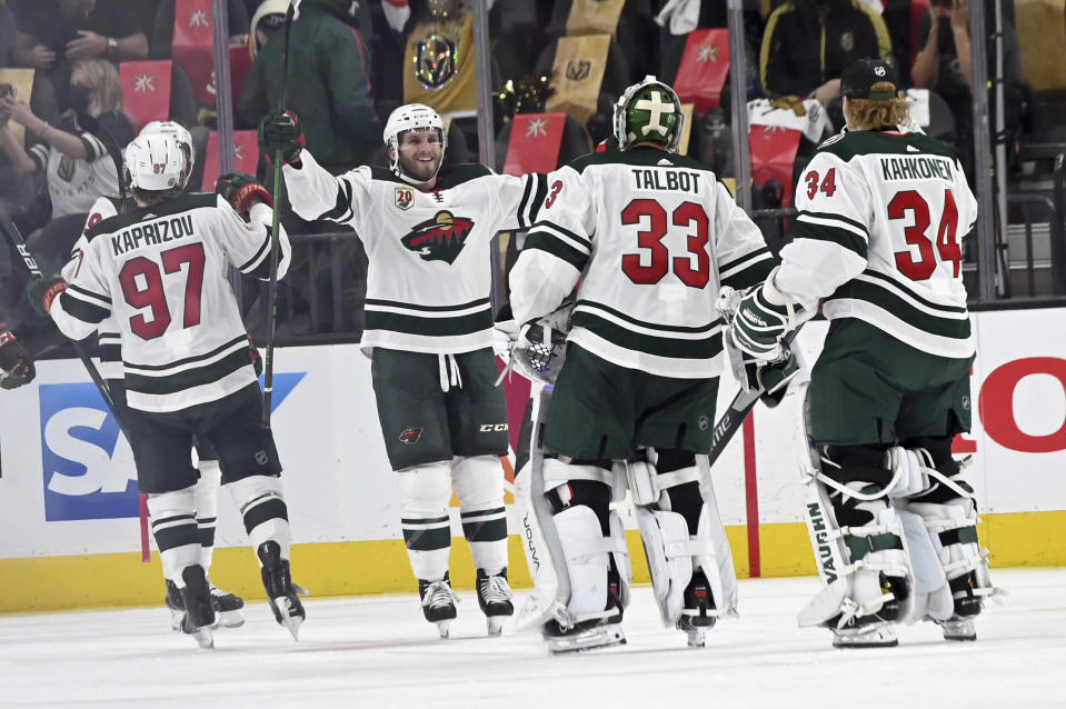 The Minnesota Wild celebrate their overtime victory over the Vegas Golden Knights in Game 1 of a first-round NHL hockey playoff series Sunday, May 16, 2021, in Las Vegas. (AP Photo/David Becker)