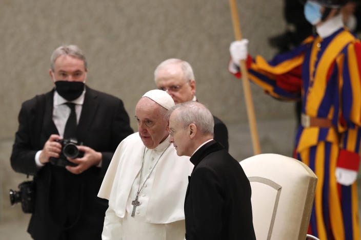 "Pope Francis shares a word with Monsignor Luis Maria Rodrigo Ewart as he arrives in the Paul VI Hall at the Vatican for his weekly general audience, Wednesday, Oct. 28, 2020. A Vatican official who is a key member of Francis' COVID-19 response commission, the Rev. Augusto Zampini, acknowledged Tuesday that at age 83 and with part of his lung removed after an illness in his youth, Francis would be at high risk for complications if he were to become infected. Zampini said he hoped Francis would don a mask at least when he greeted people during the general audience. ""We are working on that,"" he said. (AP Photo/Alessandra Tarantino)"