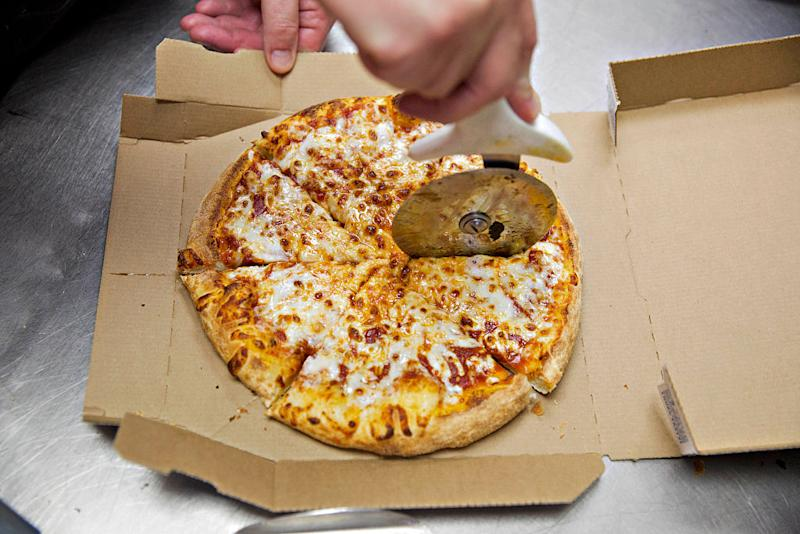 A pizza is sliced at a Domino's Pizza restaurant in Rantoul, Illinois, U.S., on Thursday, Oct. 8, 2015. Following its quarterly earnings release Wednesday, Domino's Pizza Inc. fell the most in almost two years after foreign-exchange rate moves and an insurance charge weighed on third-quarter profit. Despite the earnings miss, same-store sales in the quarter were strong, rising 10.5 percent in the U.S. and 7.7 percent internationally. Photographer: Daniel Acker/Bloomberg