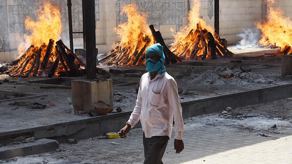 A man, pictured here walking past multiple funeral pyres of Covid-19 victims in India.
