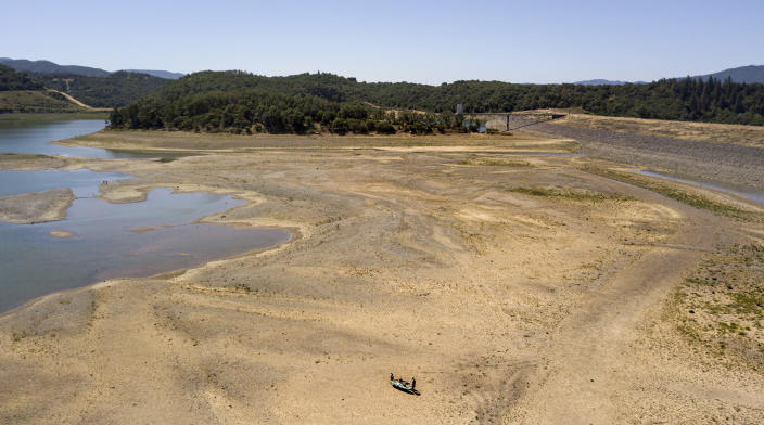 Kayakers make a long trek to the water's edge at a drought-stricken Lake Mendocino, currently at 29% of normal capacity, in Ukiah, Calif., Sunday, May 23, 2021. California Gov. Gavin Newsom declared a drought emergency for most of the state. (AP Photo/Josh Edelson)