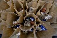 Bagged lunches await stapling before being distributed to students at the county's Tri-Plex Campus involving the students from the Jefferson County Elementary School, the Jefferson County Upper Elementary School and the Jefferson County Junior High School on Wednesday, March 3, 2021 in Fayette, Miss. As one of the most food insecure counties in the United States, many families and their children come to depend on the free meals as a means of daily sustenance. (AP Photo/Rogelio V. Solis)