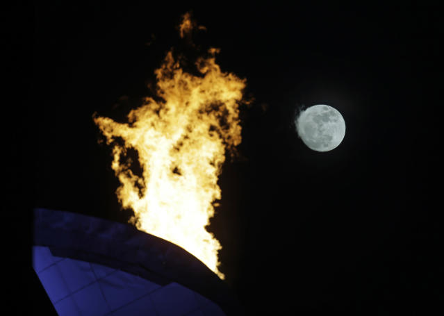 The moon is seen rising past the flame from the Olympic cauldron at the 2014 Winter Olympics, Thursday, Feb. 13, 2014, in Sochi, Russia. (AP Photo/Morry Gash)