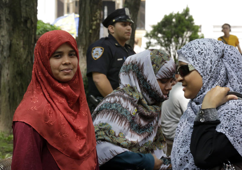Three Muslim women get together on a plaza at a gathering in front of New York City Police Department headquarters, Tuesday, June 18, 2013. In a lawsuit filed Tuesday, civil rights lawyers urged a U.S. judge to declare the NYPD's widespread spying programs directed at Muslims to be unconstitutional, order police to stop their surveillance and destroy any records in police files.(AP Photo/Richard Drew)