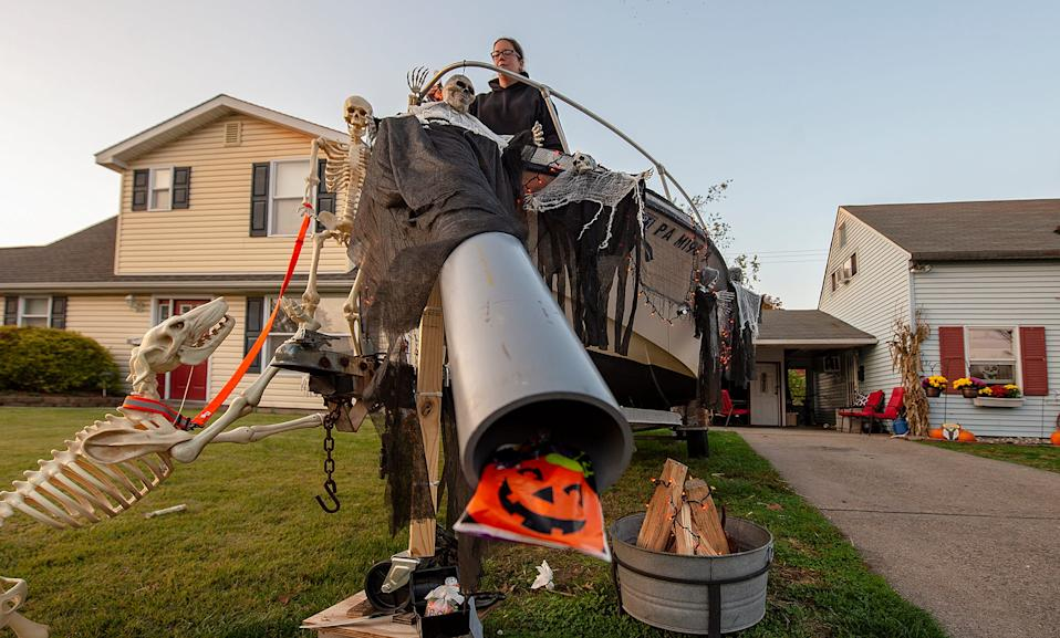 Heather Schrey, of Levittown, Penn., gets ready for Halloween during the COVID-19 pandemic, by testing the chute that candy, and ghost pops will slide through for the trick-or-treaters.