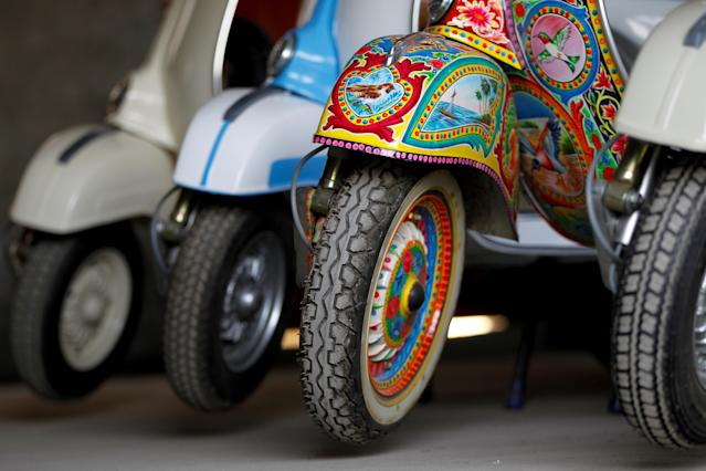<p>A restored Vespa scooter painted in Pakistani truck art style, is parked alongside traditionally-coloured scooters at a Vespa restoration and repair workshop in Islamabad, Pakistan Feb. 27, 2018. (Photo: Caren Firouz/Reuters) </p>