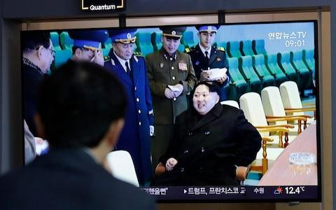 """A man watches a TV news programme reporting about North Korea's test-fire of a """"new-type tactical guided weapon"""" - Credit: AP"""