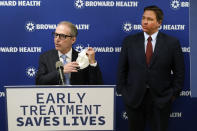 Broward Health CEO Shane Strum, leftr, takes off his mask as he speaks at a news conference alongside Florida Gov. Ron DeSantis, right, Thursday, Sept. 16, 2021, at the Broward Health Medical Center in Fort Lauderdale, Fla. DeSantis was there to promote the use of monoclonal antibody treatments for those infected with COVID-19. (AP Photo/Wilfredo Lee)