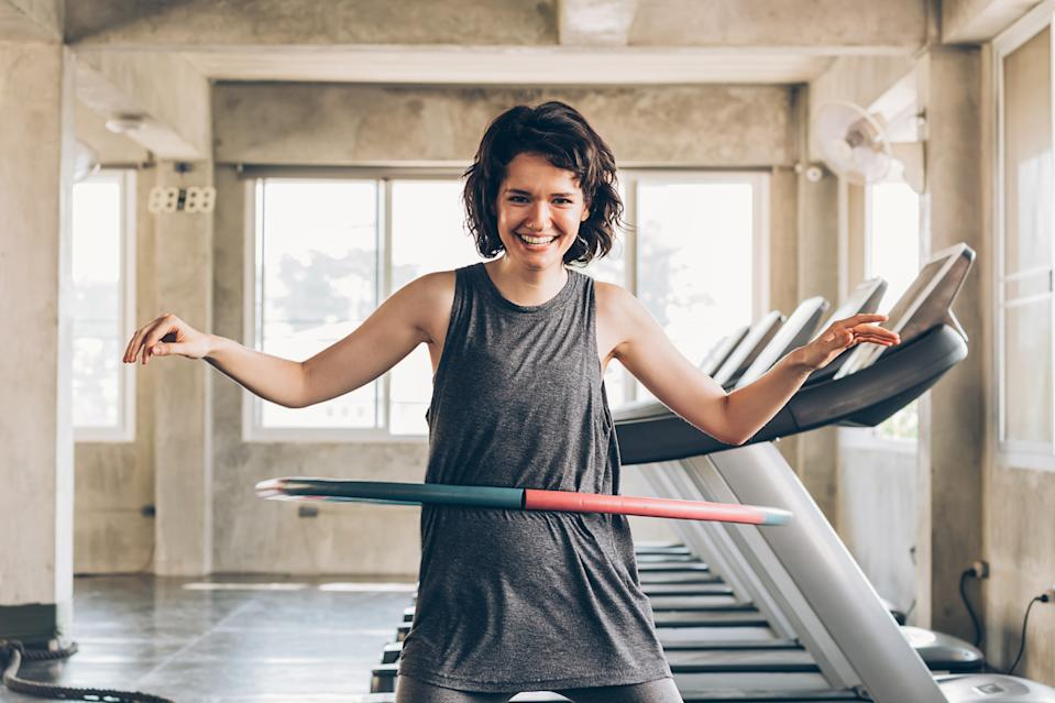 Beautiful young smiling happy Caucasian sporty woman with short hair playing hula hoop inside gym studio with treadmills behind - fun workout fitness portrait concept