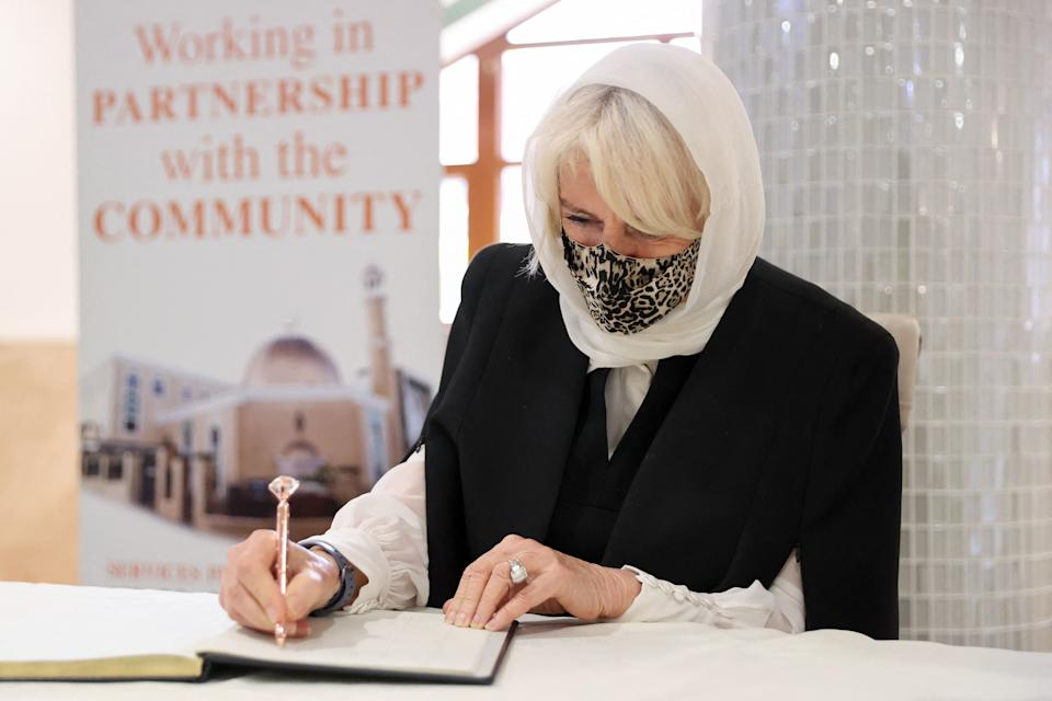 Britain's Camilla, Duchess of Cornwall signs the visitors' book during a visit to learn how the  London Islamic Cultural Society has supported the local community through the coronavirus pandemic, at Wightman Road Mosque in north London on April 7, 2021. (Photo by Chris Jackson / POOL / AFP) (Photo by CHRIS JACKSON/POOL/AFP via Getty Images)
