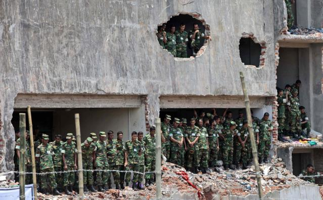 Bangladesh army soldiers stand at the wreckage of a Bangladeshi garment factory building to offer prayers for the souls of the 1,127 people who died in the structure's collapse last month, in Savar, Bangladesh, Tuesday, May 14, 2013. The Islamic prayer service was held a day after the army ended the nearly three-week, painstaking search for bodies among the rubble of the worst tragedy in the history of the global garment industry and turned control of the site over to the civilian government for cleanup. (AP Photo/A.M. Ahad)