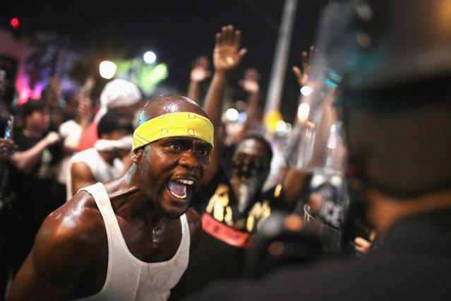 <p>SEPT. 16, 2017 – Demonstrators confront police while protesting the acquittal of former St. Louis police officer Jason Stockley in St. Louis, Missouri. Dozens of business windows were smashed and at least two police cars were damaged during a second day of protests following the acquittal of Stockley, who was been charged with first-degree murder last year following the 2011 on-duty shooting of Anthony Lamar Smith. (Photo: Scott Olson/Getty Images) </p>