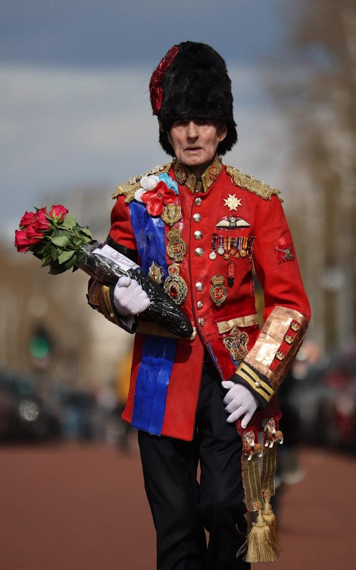 Elderly civilians dressed in vintage ceremonial military uniform style costumes carry floral compliments outside Buckingham Palace.  -Dunky Wood / Getty Images & # xa0;