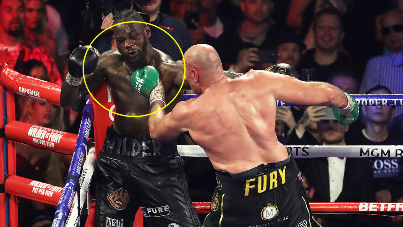 Tyson Fury punches Deontay Wilder in the chest.