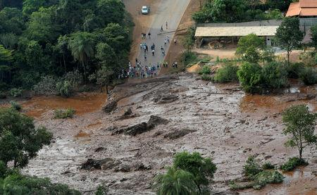 FILE PHOTO: Residents are seen in an area next to a dam owned by Brazilian miner Vale SA that burst