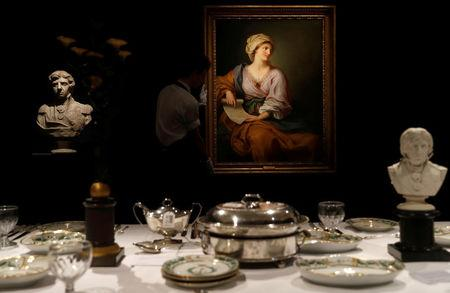 A member of Sotheby's staff poses for a photograph with a  portrait of Emma Hamilton which forms part of the sale of items celebrating Nelson's Legend, including a dinner set called the Matcham desert service, in London, Britain January 11, 2018.  REUTERS/Peter Nicholls