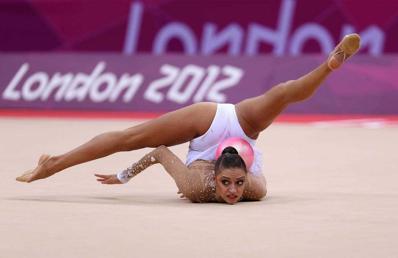 LONDON, ENGLAND - AUGUST 09:  Evgeniya Kanaeva of Russia performs with the ball during the Rhythmic Gymnastics qualification on Day 13 of the London 2012 Olympics Games at Wembley Arena on August 9, 2012 in London, England.  (Photo by Julian Finney/Getty Images)