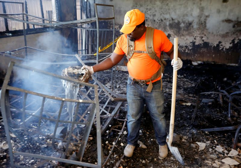 A civil protection worker pours water over burning debris inside a bedroom at an orphanage after it was destroyed in a fire, in Port-au-Prince