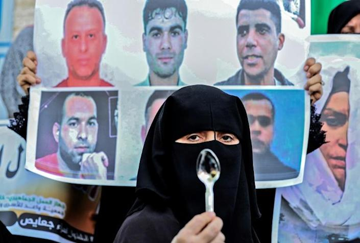 A demonstrator holds up a spoon, a makeshift tool used by six Palestinian militants who escaped from Israel's Gilboa prison, during a solidarity rally on September 8. They have all been recaptured since (AFP/SAID KHATIB)