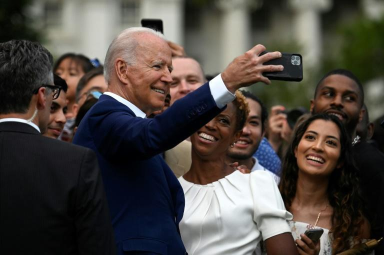 US President Joe Biden poses for a selfie with guests after delivering a speech during Independence Day celebrations on the South Lawn of the White House