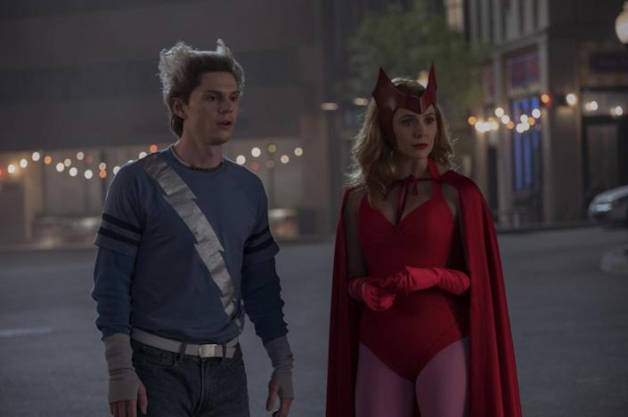 Evan Peters in a blue top with a silver lightning bolt and Elizabeth Olsen in a red leotard, gloves and cape in a street.
