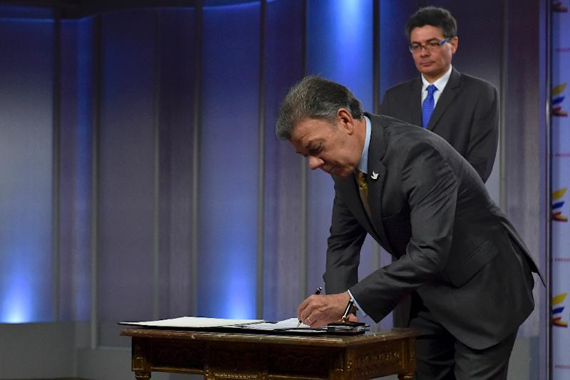 Handout picture from the Colombian Presidency shows President Juan Manuel Santos signing the decree legalizing the use of medical marijuana, next to Minister of Health Alejandro Gaviria, in Bogota on December 22, 2015 (AFP Photo/Juan Pablo Bello)