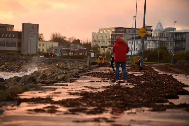 <p>People walk on a seaweed-covered path during Storm Ophelia in Galway, Ireland, Oct.16, 2017. (Photo: Clodagh Kilcoyne/Reuters) </p>