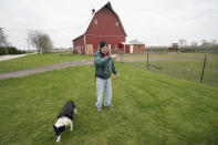 CORRECTS YEARS OF FARMING TO 43 INSTEAD OF 45 - Morey Hill speaks about his farming operation as his dog Skylar walks past, Friday, April 16, 2021, near Madrid, Iowa. In 43 years of farming, Hill had seen crop-destroying weather, rock-bottom prices, trade fights and surges in government aid, but not until last year had he endured it all in one season. Now, as Hill and other farmers begin planting the nation's dominant crops of corn and soybeans, they're dealing with another shift _ the strongest prices in years and a chance to put much of the recent stomach-churning uncertainty behind them. (AP Photo/Charlie Neibergall)