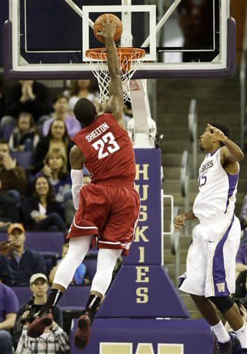 Washington State's D.J. Shelton (23) dunks as Washington's Scott Suggs, right, looks on in the first half of an NCAA college basketball game on Sunday, March 3, 2013, in Seattle. (AP Photo/Ted S. Warren)
