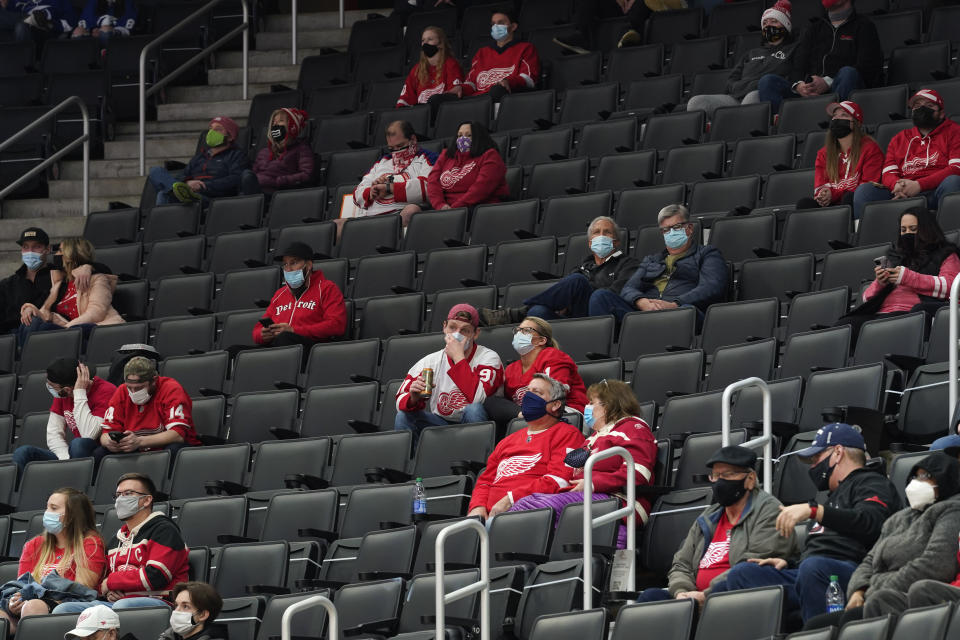Fans sit socially distanced during the second period of an NHL hockey game between the Detroit Red Wings and Tampa Bay Lightning, Tuesday, March 9, 2021, in Detroit. (AP Photo/Paul Sancya)