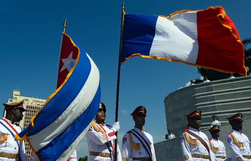"""Cuban honor guards flutter French and Cuban flags during a wreath laying ceremony at the """"Jose Marti"""" Memorial in Revolution Square in Havana on May 11, 2015, during French President Francois Hollande's visit (AFP Photo/Alain Jocard)"""
