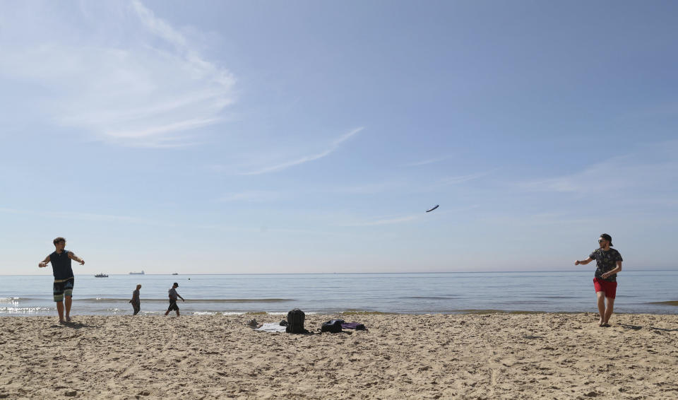 People play with a frisbee on the beach on a sunny day, in Bournemouth, England, Wednesday, May 20, 2020. Lockdown restrictions due to the coronavirus outbreak have been relaxed allowing unlimited outdoor exercise and activities such as sunbathing. (Andrew Matthews/PA via AP)