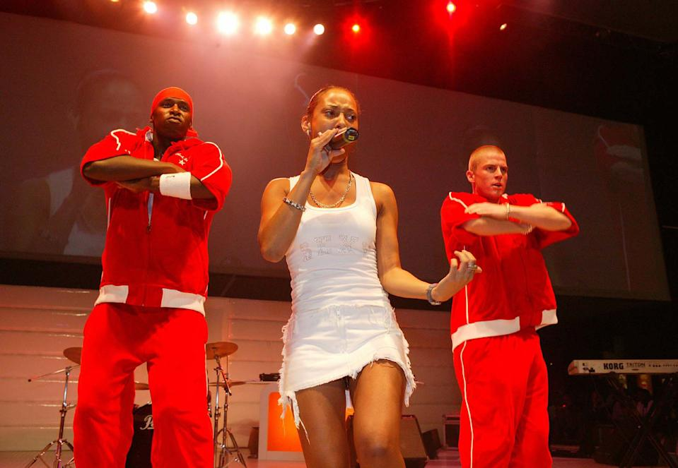 "LONDON - AUGUST 30: Singer Lisa Maffia (C) performs live on stage at the ""Sony Playstation 2 Exhibition"" at the Earls Court Exhibition Centre August 30, 2003 in London, England. (Photo by Jo Hale/Getty Images)"