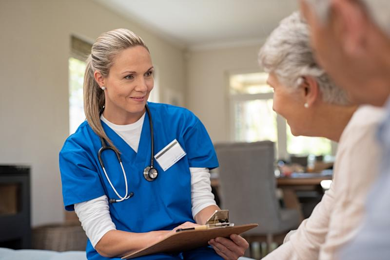 A woman in hospital scrubs with a stethoscope around her neck speaking with a gray-haired couple.