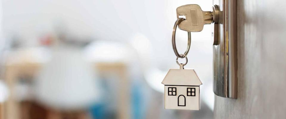 Key with house-shaped key ring in the door lock. Buy a new home concept. Real estate market.