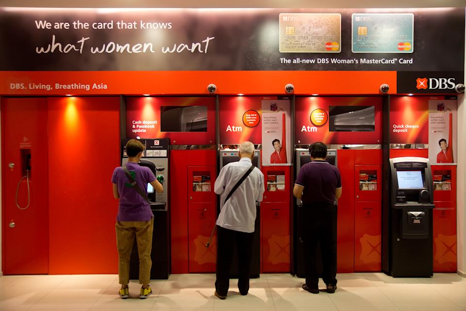 Customers drawing money from DBS ATM machines