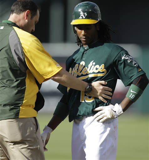 Oakland Athletics' Jemile Weeks, right, is looked at by a trainer during the second inning of a baseball game against the Detroit Tigers, Saturday, May 12, 2012, in Oakland, Calif. Weeks later left the game with an ankle injury. (AP Photo/Ben Margot)