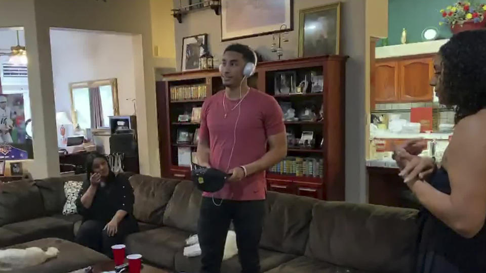 Jordan Love watches TV during the NFL draft, with a hat in his hand and headphones on.
